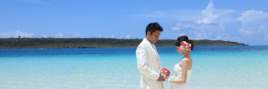 Noivos à beira do mar, vestidos em branco, segurando mãos com buquê.