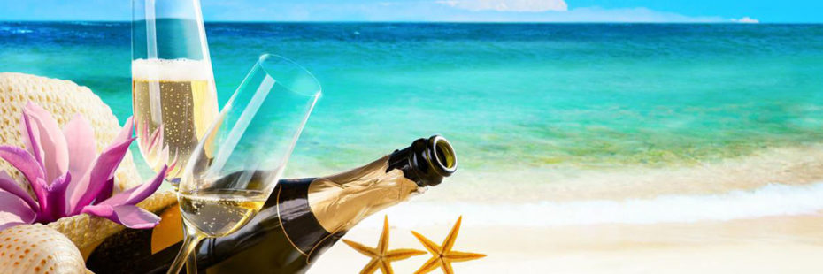 Garrafa de champagne, duas taças e demais decorações de praia à beira do mar, na faixa de areia, imagem em destaque do blog da Pousada dos Sonhos