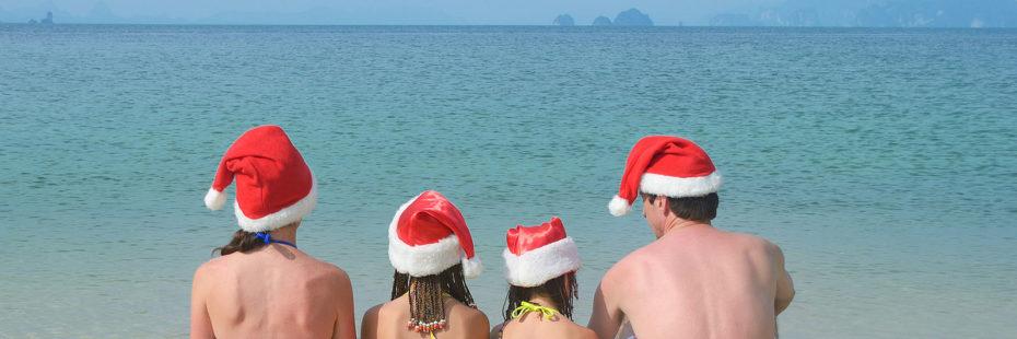 Família na beira do mar usando gorros natalinos