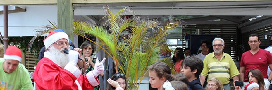 Diversas crianças aglomeradas frente ao restaurante da Pousada dos Sonhos para receber seus presentes do Papai Noel