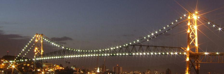 Ponte Hercílio Luz em Florianópolis à noite, iluminada, em destaque para post do blog da Pousada dos Sonhos em Jurerê, Florianópolis.