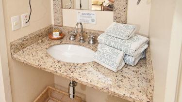 Detalhe da pia do banheiro do apartamento duplex da Pousada dos Sonhos. Diversas toalhas e sabonetes, água fria e quente e secador de cabelos.