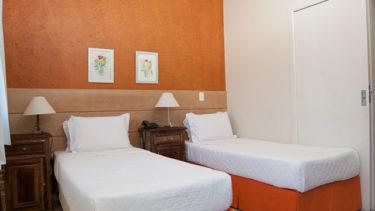 Quarto de solteiro do apartamento duplex da Pousada dos Sonhos com duas camas que podem ser unidas em um cama de casal. Ar condcionado incluso, dois criados mudos e televisão a cabo.