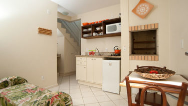 Entrada do apartamento duplex da Pousada dos Sonhos com visão da cozinha integrada com sala de estar.