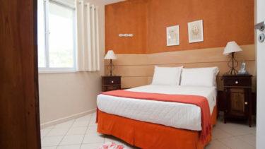 O quarto de casal no apartamento superior duplex da Pousada dos Sonhos, conta com ar condicionado, ampla janela e um ambiente privado e discreto com vista lateral para o mar de Jurerê.