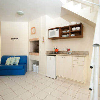 O apartamento superior duplex é compacto, trazendo uma sala integrada com cozinha, incluindo churrasqueira interna para aquele delicioso churrasco de domingo, assim como escada levando aos quartos no nível superior.