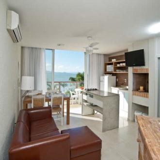 Sala e cozinha integrada da cabana super luxo da Pousada dos Sonhos em Jurerê, Florianópolis. Conforto e praticidade no seu momento de relaxamento.