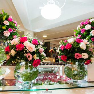 Belos buquês de flores decoram uma mesa à noite no interior da Pousada dos Sonhos, enquanto a festa acontece do lado de fora; seu casamento inesquecível na Pousada dos Sonhos em Florianópolis!