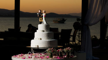Decoração com pétalas de flores ao redor de um bolo decorativo com miniaturas do casal prestes a se casar na beira do mar de Jurerê, em Florianópolis, na Pousada dos Sonhos.