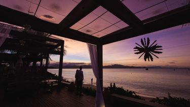 Casal em pé à beira do mar de Jurerê, no deque frente à praia da Pousada dos Sonhos em Florianópolis, contemplando uma cerimônia de casamento neste belo cenário; assim como você, esse sonho um dia pode se tornar realidade!
