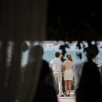 Tarde ensolarada, o mar azul, manso, ao fundo. Convidados ao redor, e a câmera ao fundo, nas sombras, presenciando tudo de longe, arrebatada com a visão fenomenal da praia neste casamento à beira do mar de Jurerê, na estrutura da Pousada dos Sonhos em Florianópolis!