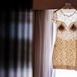 Um leve vestido de noiva em destaque contra a luz da janela em um quarto escurecido pelas cortinas na Pousada dos Sonhos, localizada na beira da praia de Jurerê em Florianópolis.