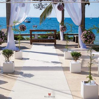 O altar para cerimônia de casamento à beira do Mar de Jurerê em Florianópolis, agora decorada para outro casamento, cadeiras brancas ao redor do altar, arranjos delicados e o mar de azul vibrante ao fundo, complementando o cenário exclusivo da Pousada dos Sonhos.