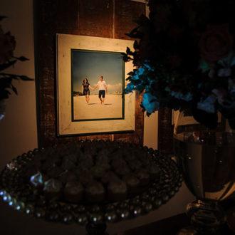 Um foco de luz destaca foco do casal de mãos dadas caminhando pela praia, enquanto que a mesa de doces complementa a imagem, banhada em sombras. Arranjos de flores e uma bandeja de doces podem ser vistos discretamente com reflexos das luzes ao redor. Decoração de casamento na Pousada dos Sonhos, na praia de Jurerê, Florianópolis.