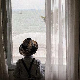 A visão do oceano, um barco solitário a flutuar pelo mar, e o deque coberto logo abaixo é admirado por um menino; a juventude também fica arrebatada com essa beleza única que é Jurerê em Florianópolis, uma experiência especial para todos os hóspedes da Pousada dos Sonhos!
