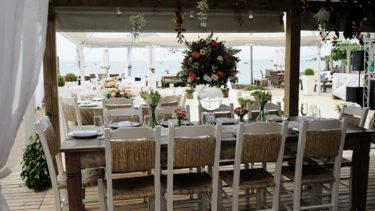 Visão geral do restaurante em direção ao mar, com o deque logo a frente, tudo decorado para receber os convidados para o casamento. Muitas flores, e a cor branca harmonizando com a vista paradisíaca logo à frente, o céu, praia e mar complementando o cenário de um casamento dos sonhos na Pousada dos Sonhos!