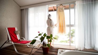 Um ar rústico, mas elegante: uma toalha vermelha se encontra na cadeira em frente a enorme janela, cortinas leves e claras introduzem um tom manso à acomodacão da Pousada dos Sonhos, a vista da praia de Jurerê em Florianópolis se estende além da janela, e por sobre o frame de madeira ao redor da banheira se encontra um pode de flor, suas folhas parecendo corações; a noiva olha pela janela com seu vestido pendurado ao seu lado, na janela, tendo saído do banho e se preparando para um dos momentos mais importantes de sua vida... em um lugar magnífico; simplesmente inesquecível!