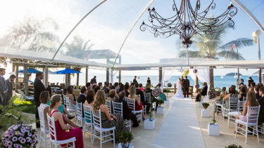 Visão geral de uma cerimönia acontecendo à beira da praia com vista para o mar de Jurerë, em Florianópolis. Todos se encontram na área externa, coberta, no final de um belo dia de sol. Ao fundo, no centro, próximo do mar, os noivos se encontram perante o altar. Um lindo lustre se encontra na parte superior da foto. Outra linda cerimônia matrimonial na Pousada dos Sonhos!