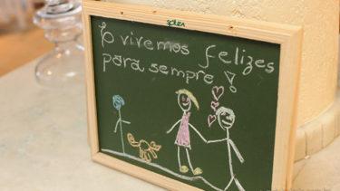 Foco em um pequeno quadro negro com um desenho de um casal, três corações rosas flutuando entre os dois, e um cachorro e um menino observam a cena logo ao lado. Acima desse desenho, se encontra a frase