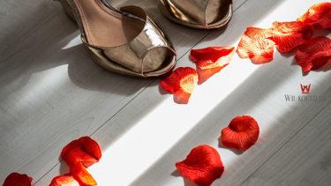Chão de madeira, dando um ar rústico à acomodação da Pousada dos Sonhos em Jurerê, Florianópolis. Sapatos dourados da noiva estão entre raios de sol que escapam por entre as frestas das cortinas, e diversas pétalas de rosas vermelhas se encontram espalhadas pelo chão, dando um clima mágico e romântico ao casamento que está prestes a acontecer na praia de Jurerê em Florianópolis.