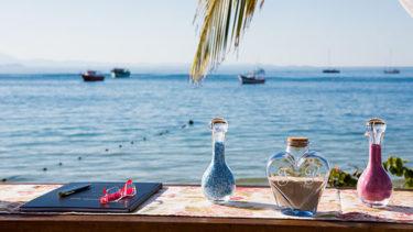 Barcos flutuam serenamente em uma tarde de sol em Jurerê, Florianópolis, com decorações e enfeites sobre o altar, assim como um par de óculos e o livro do celebrante momentos antes da cerimônia de frente para o mar na Pousada dos Sonhos