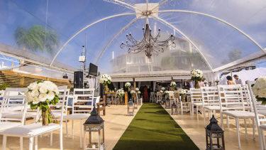 O deque frente mar da Pousada dos Sonhos em Jurerê, com diversas cadeiras, tapete verde em direção ao altar e visão geral do ambiente com vista para a pousada, num dia ensolarado de céu limpo e cores vibrantes.