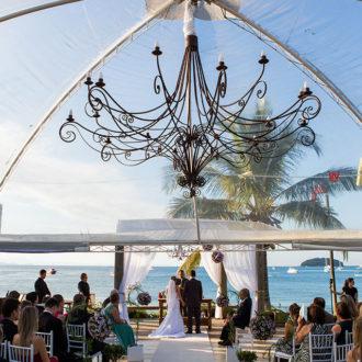 Grupo de pessoas reunidas no deque da Pousada dos Sonhos em Jurerê, Florianópolis, celebrando a união dos noivos em um cenário deslumbrante, com céu e mar azul a agraciar todos os presentes.