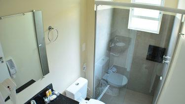 Banheiro da suíte do flat Alexandrina 3 quartos da Pousada dos Sonhos completo com toalhas, box de vidro e secador de cabelos.