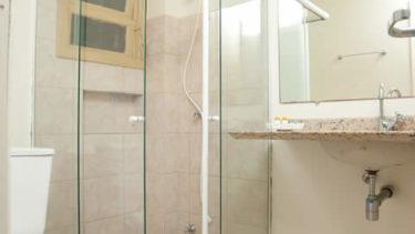 Banheiro completo com box de vidro e secador de cabelos do Flat Atlântico, localizado fora da estrutura principal da Pousada dos Sonhos em Jurerê.