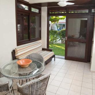 Entrada do flat Atlântico da Pousada dos Sonhos com visão da mesa, sofá e janela.