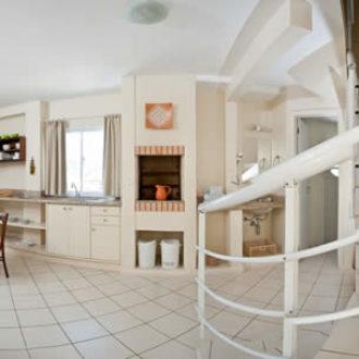Vista do apartamento luxo duplex na Pousada dos Sonhos em Jurerê, simulando entrada no mesmo: coinha, escadas e parte da sala.