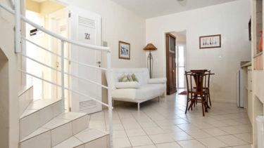 Vista da entrada do apartamento luxo duplex na estrutura da Pousada dos Sonhos em Jurerê, Florianópolis. Escadas, sofá e pequena mesa ao fundo.