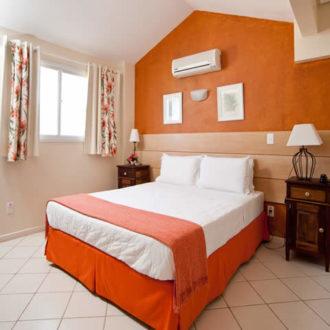 O quarto de casal do Apartamento Luxo Duplex é espaçoso e achonchegante, com tons de laranja alegrando o ambiente. A proximidade não só da praia mas de diversas outras conveniências ao redor da Pousada dos Sonhos fazem desta uma excelente escolha para você e sua família!