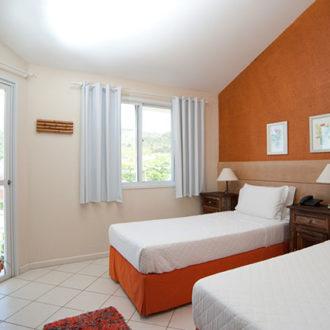 O quarto de solteiro do Apartamento Luxo Duplex tem uma pequena sacada com vista lateral para o mar de Jurerê em Florianópolis, assim como uma janela com a mesma vista. Acomodação da Pousada dos Sonhos.