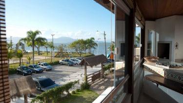 Muita luz e beleza natural entram na ampa sala de estar com sacada da Cabana Luxo; uma experiência incrível te aguarda aqui na Pousada dos Sonhos em Jurerê!