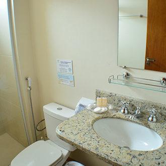 Banheiro do Flat Alexandrina da Pousada dos Sonhos em Florianópolis. Estrutura completa com box de vidro e secador de cabelos.