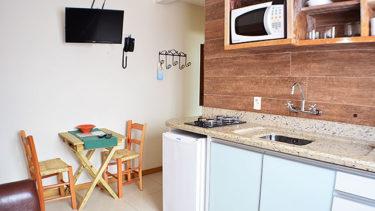 Vista da cozinha e sala integrada do flat Alexandrina 1 Quarto da Pousada dos Sonhos em Jurerê, Florianópolis com mesa, televisão, telefone e cabideiro na entrada da acomodação.