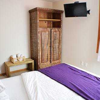 Vista de parte da cama, armário e janela do quarto do Flat Alexandrina 1 Quarto na Pousada dos Sonhos, Jurerê. Conforto e requinte rústico para seu relaxamento em Florianópolis!