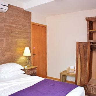 Quarto em si do Flat Alexandrina 1 Quarto com parede texturizada dando um ar rústico e elegante à acomodação. O quarto inclui armário, abajures, ar codnicionado e televisão.