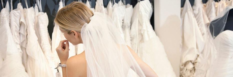 Noiva perante diversos vestidos, fazendo sua escolha e experimentando acessórios
