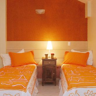 Duas camas de solteiro com parede laranja ao fundo, abajur ligado e lençóis laranjas na Pousada dos Sonhos, Apartamento Duplex.