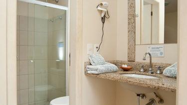 Um banheiro moderno, com porta de vidro para o chuveiro do Apartamento VIsta Lateral da Pousada dos Sonhos em Jurerê, Florianópolis