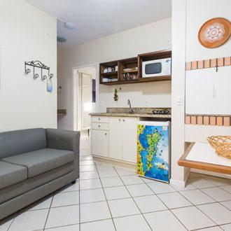 Sofá confortável, cozinha compacta com praticidade para mater o foco de sua viagem no descanso e entretenimento seu e de sua família do Apartamento Vista Lateral da Pousada dos Sonhos em Jurerê em Florianópolis.
