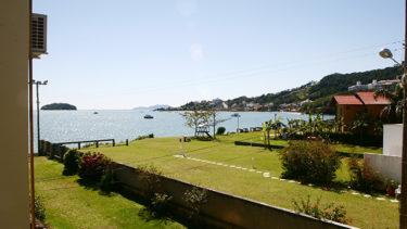 O Apartamento Vista Lateral tem uma sacada com muito verde ao redor e vista do mar de Jurerê e a famosa ilha do Francês em Florianópolis, na Pousada dos Sonhos!