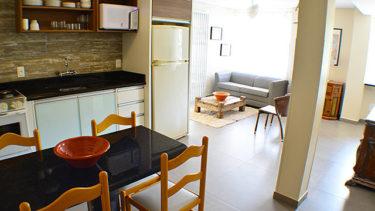 Cozinha e sala de estar vistas do corredor interno para os quartos do Flat Alexandrina 3 Quartos da Pousada dos Sonhos. Mesa de jantar, sofá com mesinha de centro, cadeiras, armários e balcões tornam esta acomodação aconchegante.