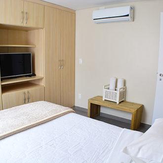 O quarto de casal do flat Alexandrina 3 quartos da Pousada dos Sonhos conta com um armário ccompleto, televisão tela plana e ar condicionado. Conforto e bastante iluminação natural para uma estadia dos sonhos em Florianópolis