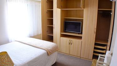 As portas do armário do quarto de casal do Flat Alexandrina 3 quartos da Pousada dos Sonhos em Jurerê estáo abertas para dar uma noção do espaço interno e todas as separações para os diferentes estilos de roupas.