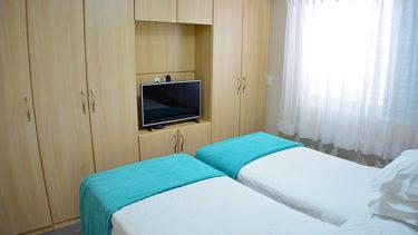 O quarto de solteiro do flat Alexandrina 3 quartos da Pousada dos Sonhos possui duas camas de solteiro que podem ser unidas em uma cama de casal. Televisão e ar condicionado também estão inclusos.