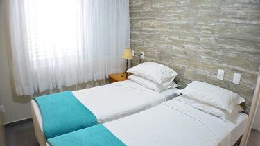 Destaque das camas do quarto de solteiro do flat Alexandrina 3 quartos da Pousada dos Sonhos em Jurerê, Florianópolis.