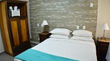 A suíte do flat Alexandrina 3 quartos da Pousada dos Sonhos tem um ar todo especial com parede ao fundo texturizada, armários rústicos e banheiro exlusivo.